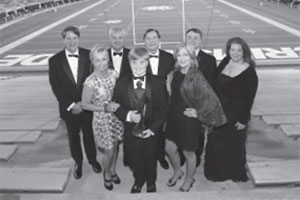 Johnny Johns posing in stand of Bryant-Denny Stadium with his family